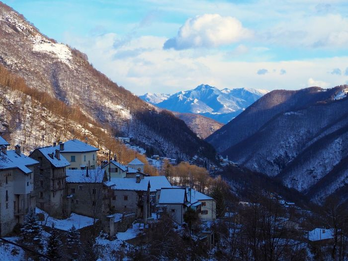 Houses by mountains against sky during winter