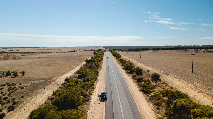 High angle view of country road against blue sky