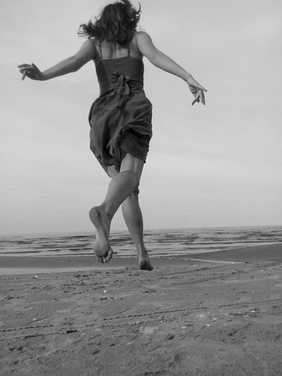 Rear view of young woman jumping on beach