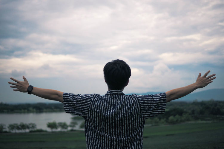 Welcome to natural land Rear View One Person Sky Human Arm Cloud - Sky Real People Arms Outstretched Nature Casual Clothing Waist Up Field Standing Lifestyles Beauty In Nature Arms Raised Freedom Outdoors Teenager Holiday Moments