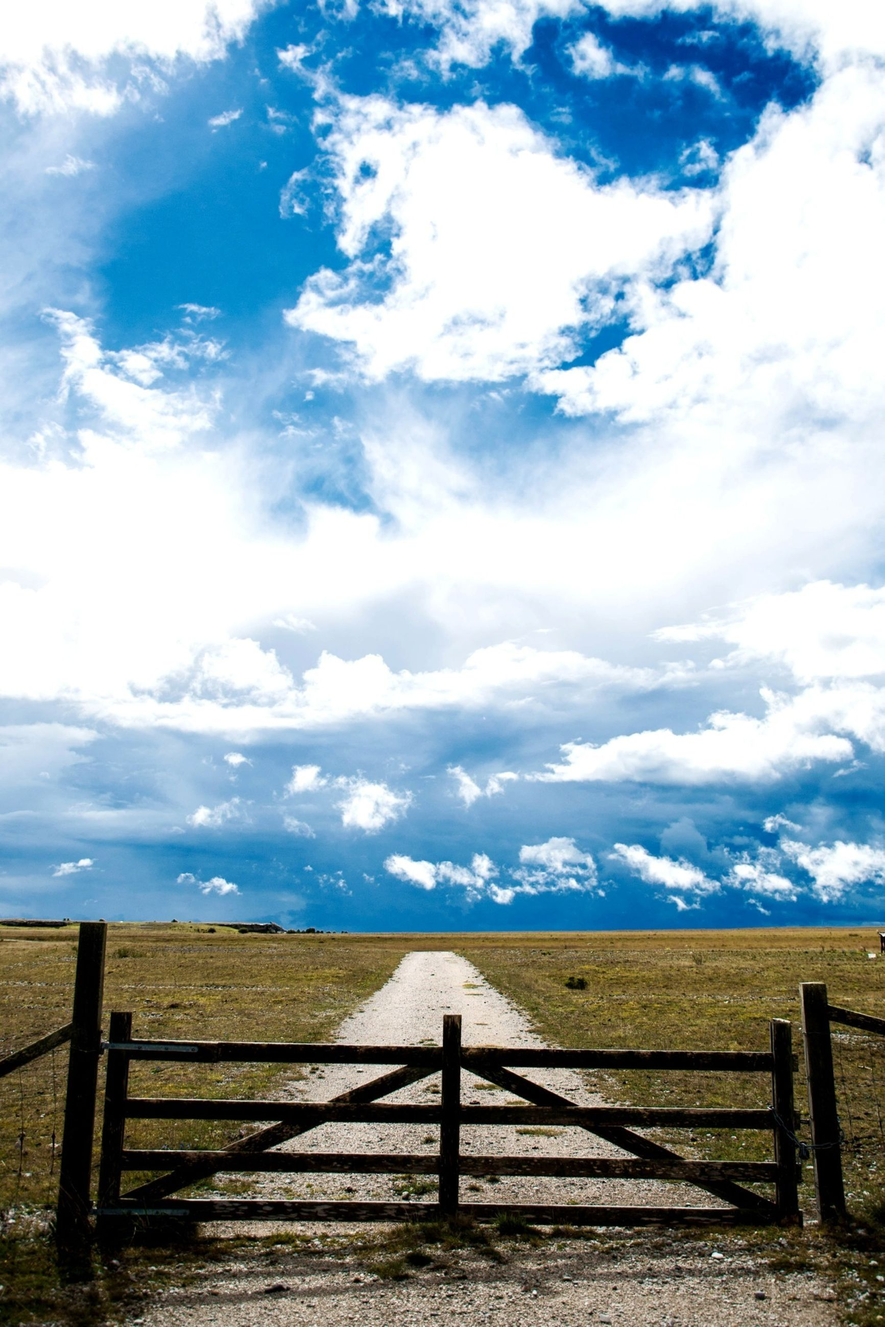 sky, railing, tranquility, tranquil scene, cloud - sky, fence, scenics, landscape, beauty in nature, cloudy, nature, cloud, field, sea, wood - material, the way forward, non-urban scene, idyllic, remote, blue