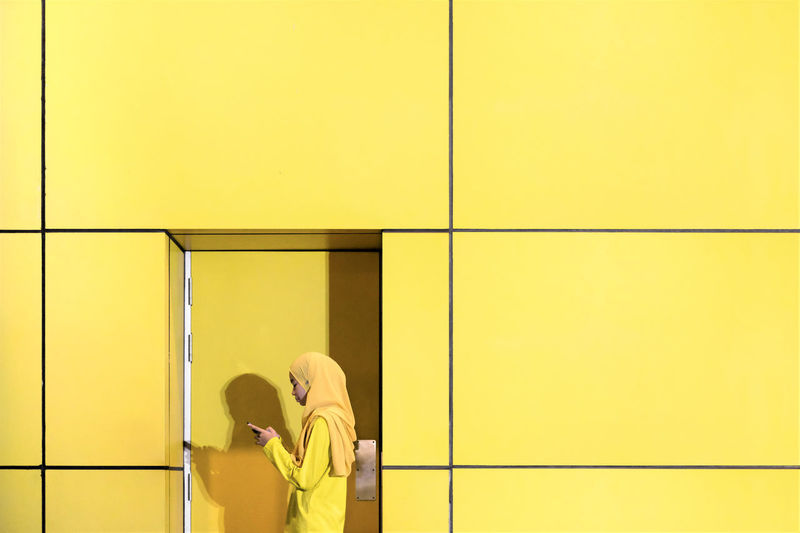 Side view of teenage girl using phone while standing by yellow wall