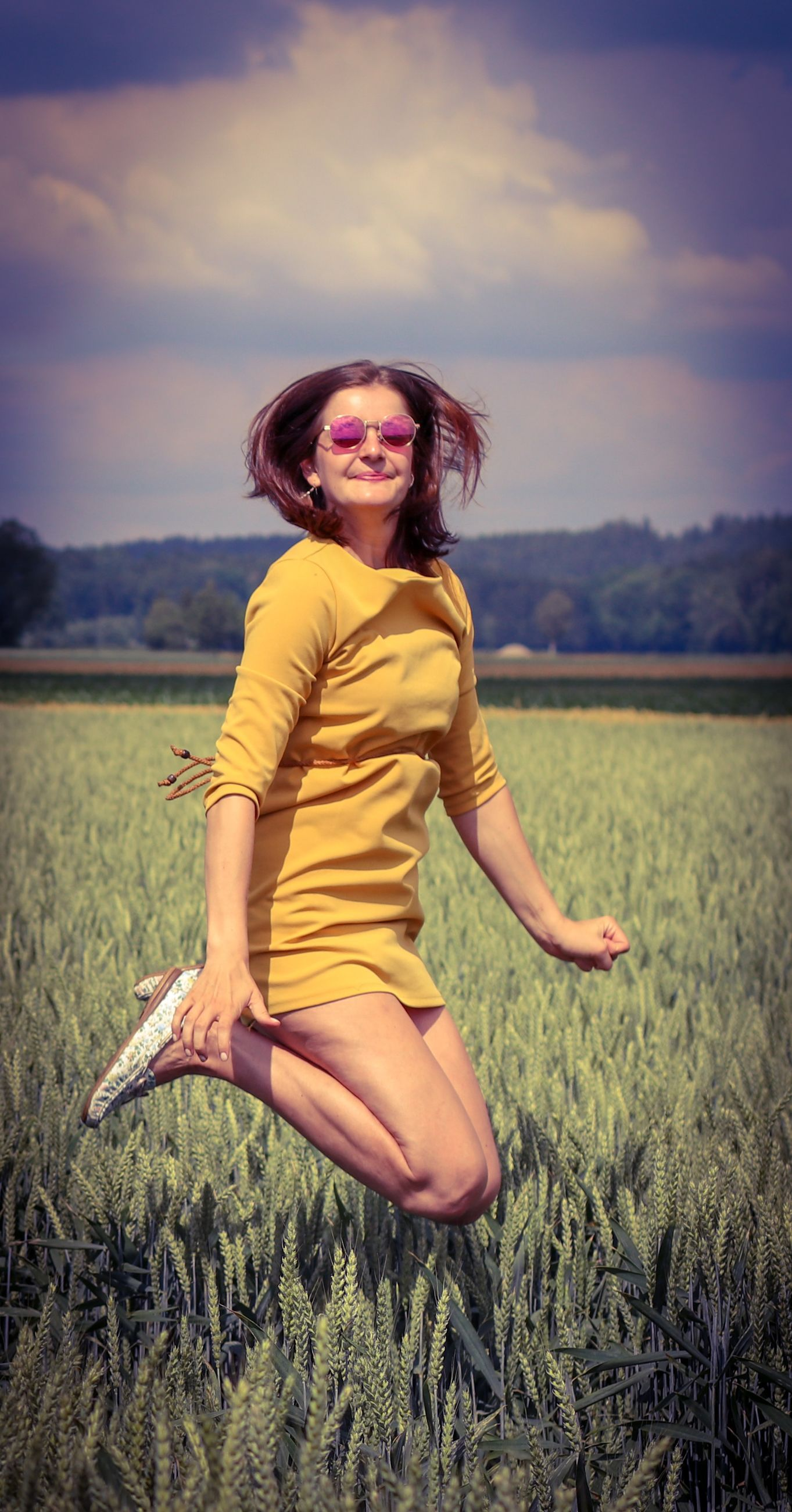 one person, field, land, sky, leisure activity, women, plant, happiness, beauty in nature, clothing, nature, smiling, cloud - sky, real people, lifestyles, grass, fashion, full length, outdoors, freedom