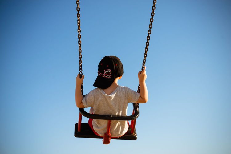 Low angle view of boy on swing at playground against clear sky