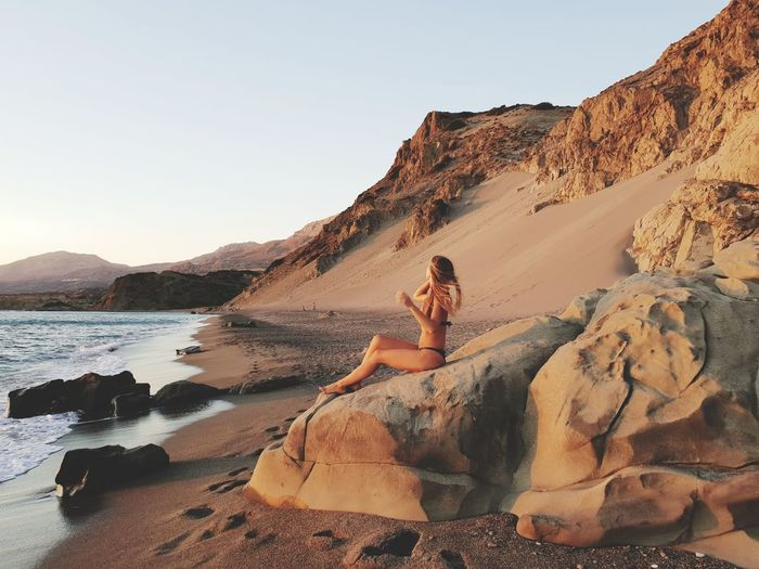 Side view of woman in bikini sitting on rock at shore