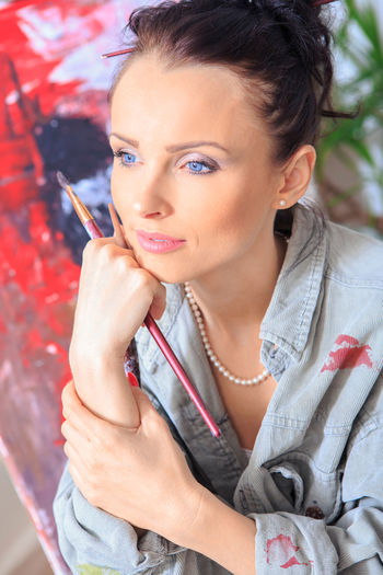 portrait of a female painter at work Adult Adult, Art, Artist, Artistic, Artwork, Beautiful, Brush, Canvas, Creative, Creativity, Drawing, Female, Girl, Hobby, Home, Interior, Lifestyle, Paint, Paintbrush, Painter, Painting, Palette, Person, Portrait, Professional, Studio, Woman, Work, Young Beautiful Woman Beauty Casual Clothing Contemplation Fashion Focus On Foreground Hairstyle Headshot Holding Indoors  Leisure Activity Lifestyles Looking At Camera Make-up One Person Portrait Real People Women Young Adult Young Women