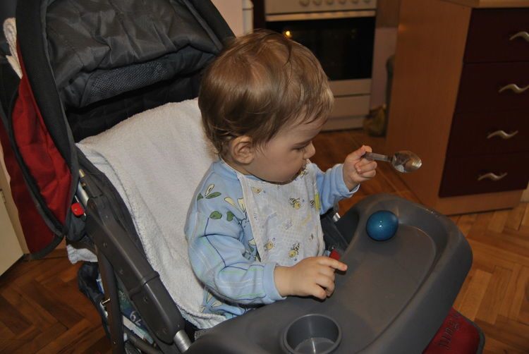 High angle view of cute boy with egg and spoon sitting on baby stroller at home