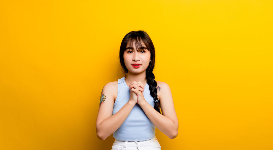 Portrait of young woman against yellow background