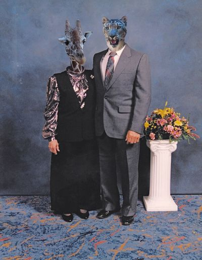 Couple wearing animal masks while standing against wall