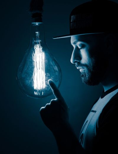 Lights out, what will tomorrow bring.. Capture Tomorrow Light Bulb Edison Bulb Illuminated One Person Holding Indoors  Glowing Dark Young Men Headshot Real People Portrait Lighting Equipment Night Technology Black Background Men Lifestyles Studio Shot Young Adult Social Issues Capture Tomorrow