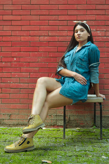 Portrait of woman sitting against wall