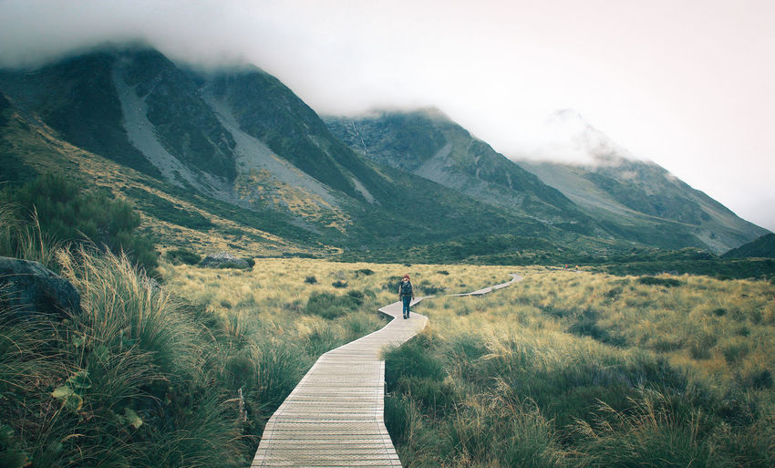 Woman walking on boardwalk leading towards mountains against sky