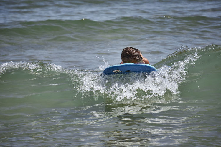 BodyBoarding Adolescence  Aquatic Sport Day Headshot Leisure Activity Lifestyles Men Motion Nature One Person Outdoors Real People Rear View Sea Sport Surfing Swimming Teenage Boys Teenager Water Waterfront Wave