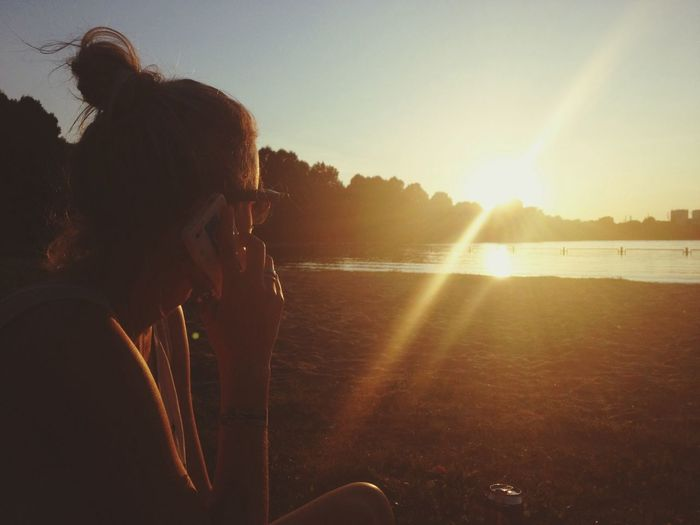 Woman answering smart phone while sitting on field by lake during sunset