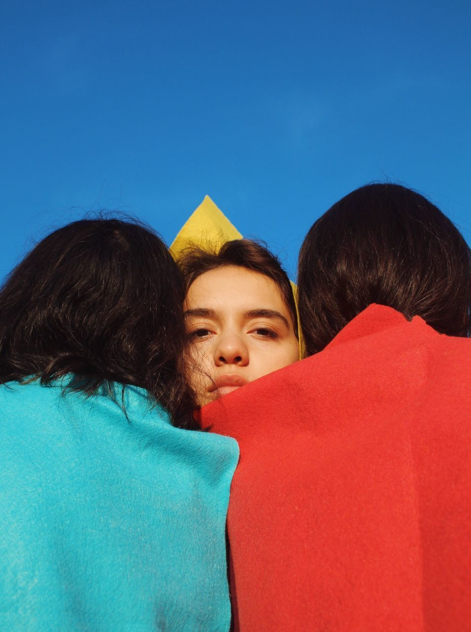 Close-Up Of Friends Against Clear Blue Sky
