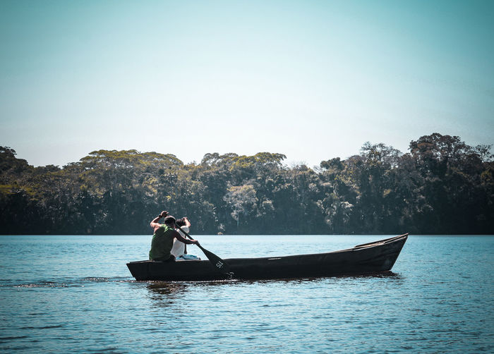Man rowing boat in sea against clear sky
