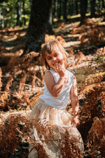 Portrait of cute girl standing in forest