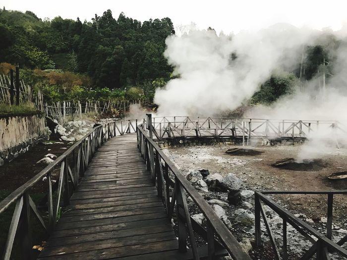 Boardwalk Amidst Smoke Emitting Hot Springs