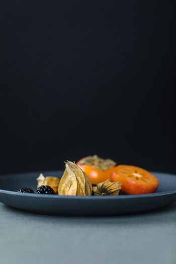Close-up of burger in plate on table against black background