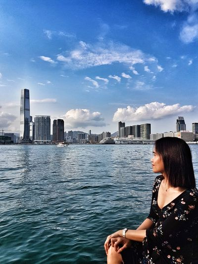 Mid adult woman sitting by river against sky in city