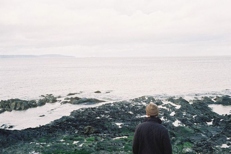 Rear view of man standing on rocky shore