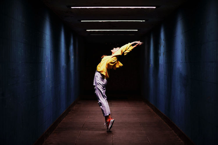 Full length of woman stretching in darkroom