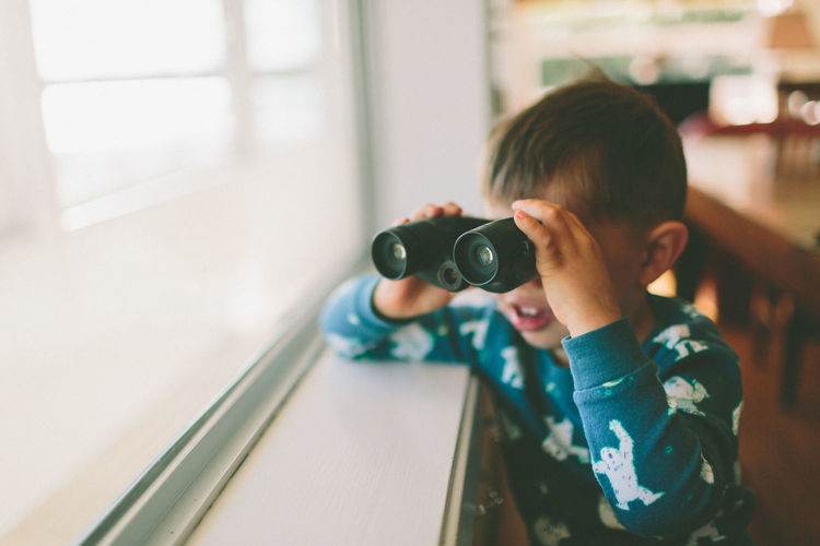 A little boy looking out the window with binoculars. Child Boys Holding Leisure Activity Lifestyles Binoculars Searching Boy Exploring Adventure