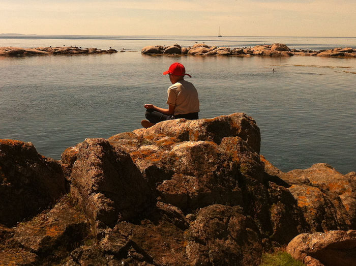 Meditation Beauty In Nature Casual Clothing Day Full Length Horizon Over Water Leisure Activity Lifestyles Meditationgrowth Nature One Person Outdoors Real People Rear View Rock - Object Scenics Sea Sitting Tranquil Scene Tranquility Water