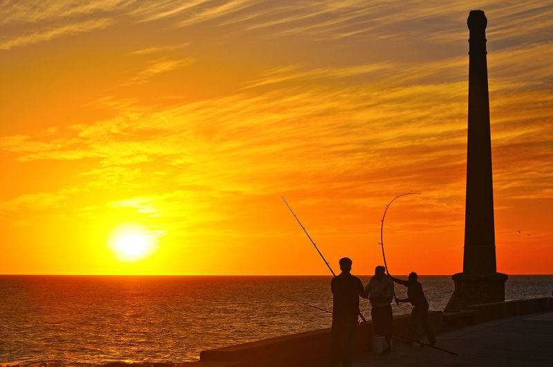 SILHOUETTE OF Men FISHING IN SEA DURING SUNSET