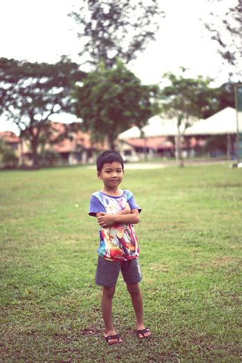 Full length portrait of cute boy with arms crossed standing on grass