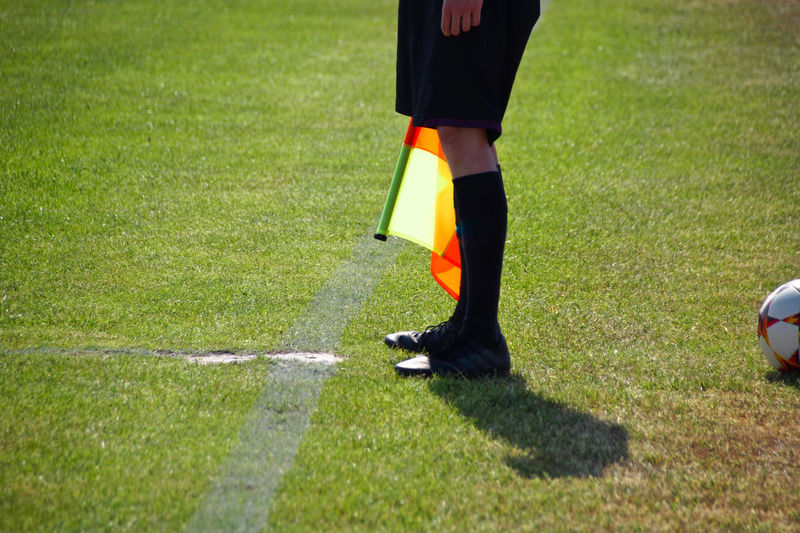 Low Section Of Referee Standing On Soccer Field