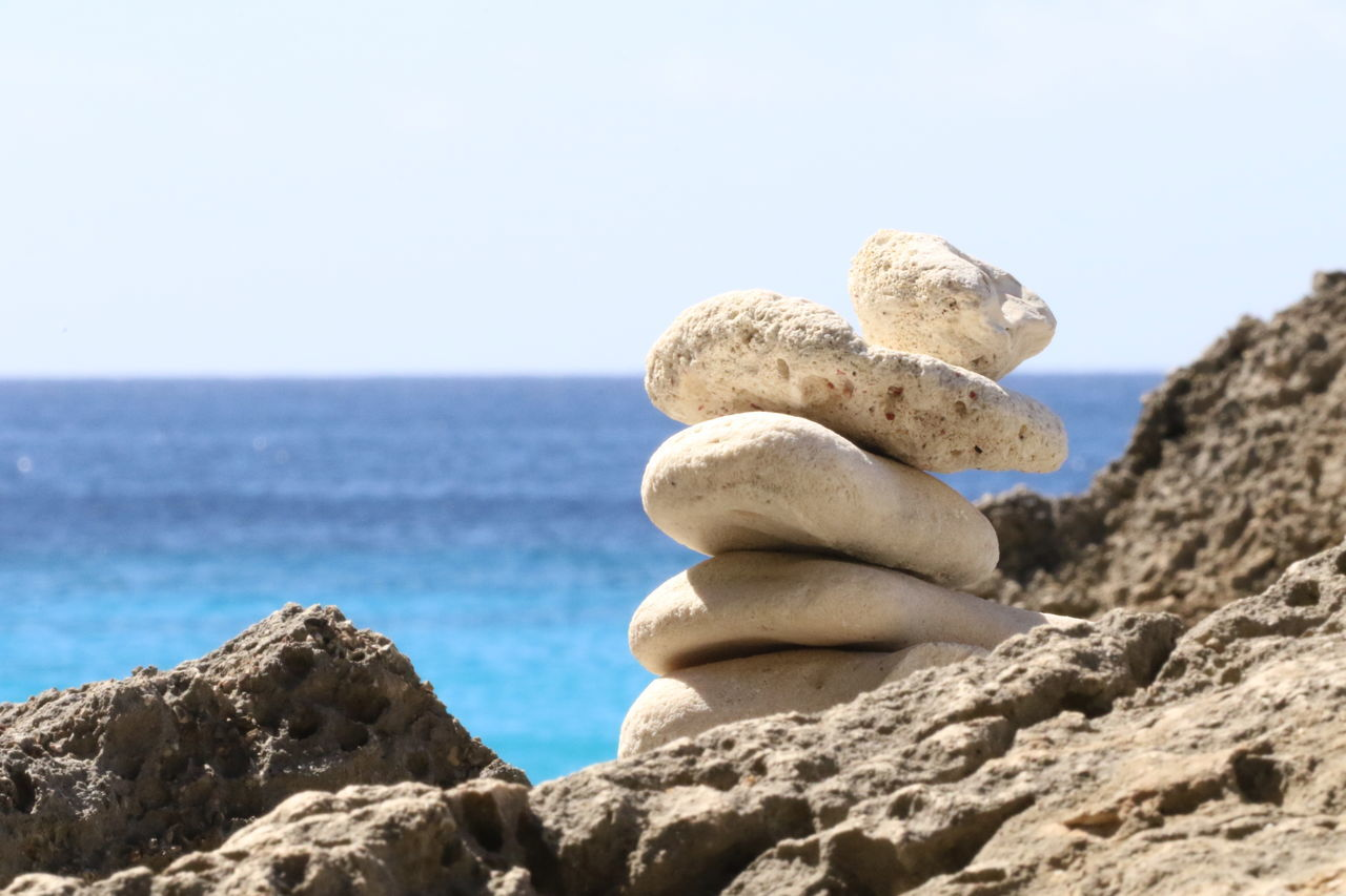 rock - object, sea, nature, rock formation, day, beauty in nature, outdoors, no people, focus on foreground, clear sky, tranquil scene, beach, low angle view, horizon over water, sky, scenics, water, close-up, animal themes