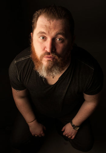 Mid Adult Man With Beard Against Black Background