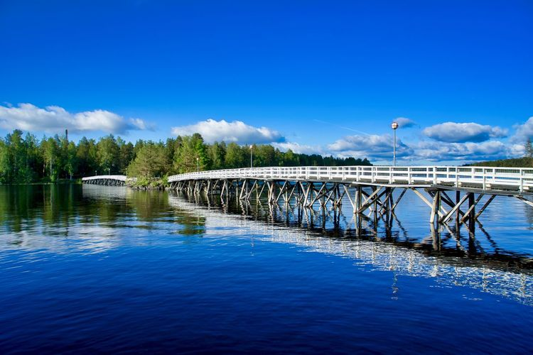 wood bridge connecting the city to a public park on an island Lake Finland Jyväskylä Summer Time  Blue Sky Blue Color Cloud - Sky Reflection Connection Horizontal Daytime Daylight Travel Destinations Romantic Water Sky Blue Bridge Architecture Built Structure Nature Waterfront Bridge - Man Made Structure No People River Day Tree Outdoors Transportation Scenics - Nature Arch Bridge