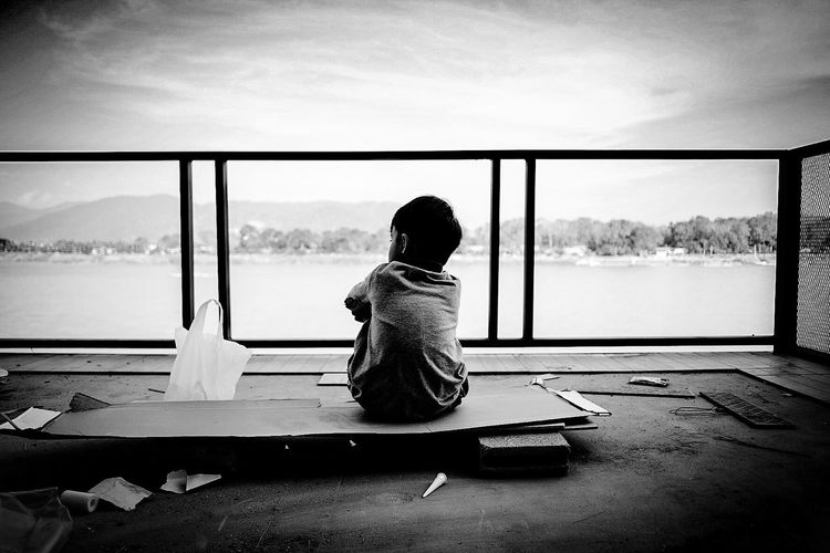 Rear View Of Child Sitting On Balcony