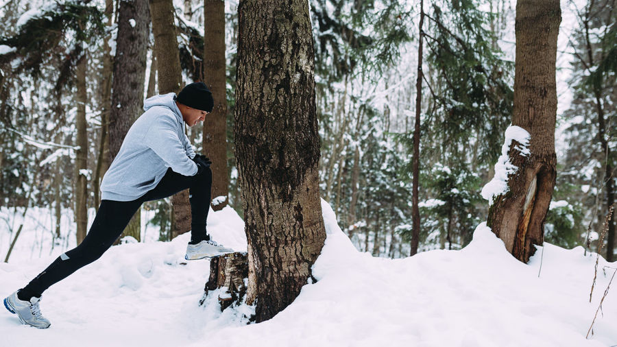 Man Exercising On Snow Covered Field During Winter
