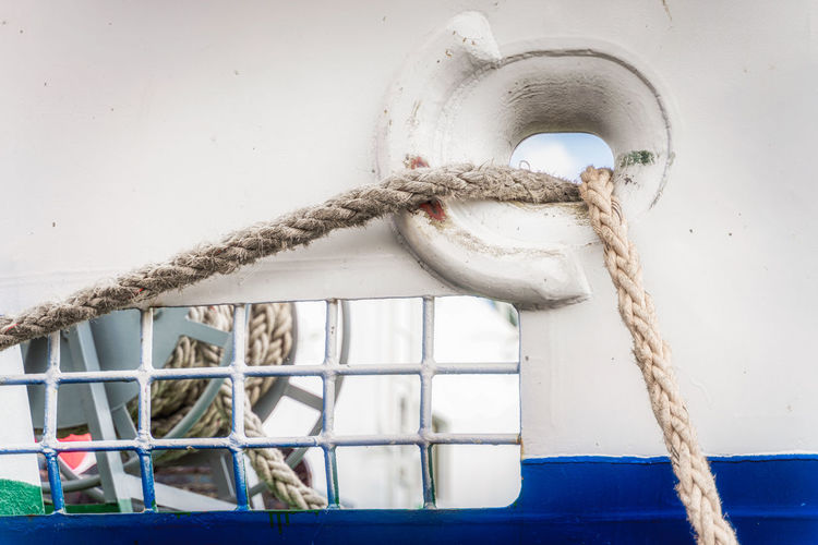 Close-up of rope tied on metal wall