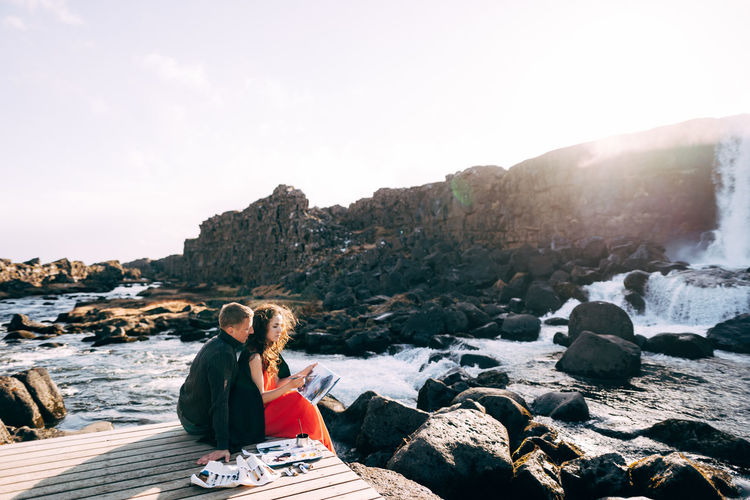 Couple sitting on jetty against sky