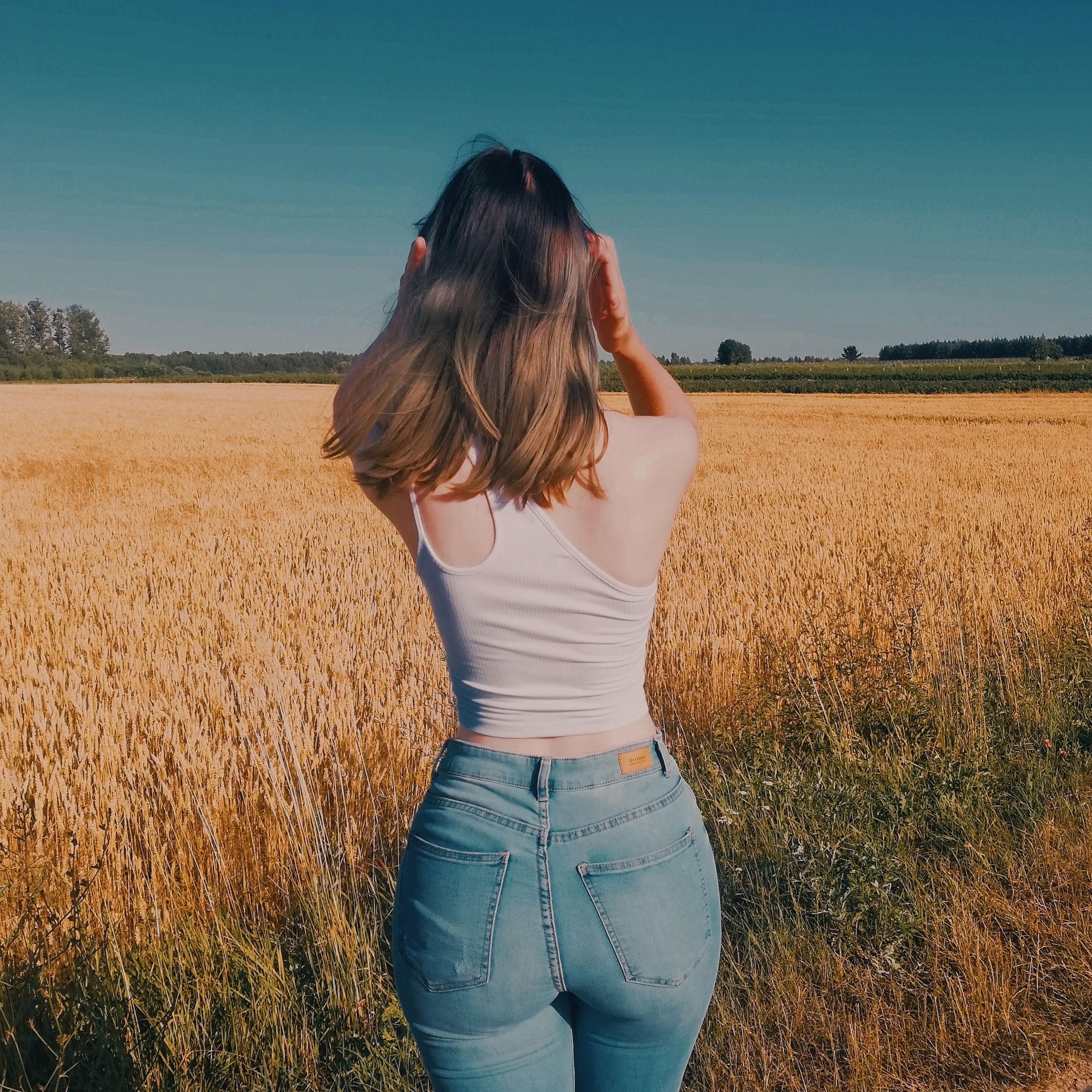 field, land, one person, real people, leisure activity, casual clothing, standing, plant, lifestyles, women, three quarter length, landscape, sky, environment, agriculture, hairstyle, nature, hair, day, outdoors