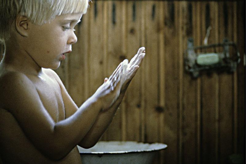 Shirtless boy washing hands in sauna