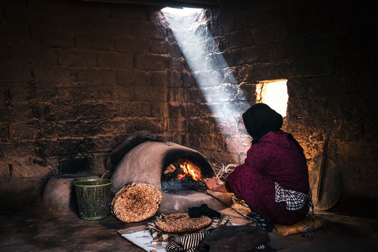 Midsection of woman preparing food against wall