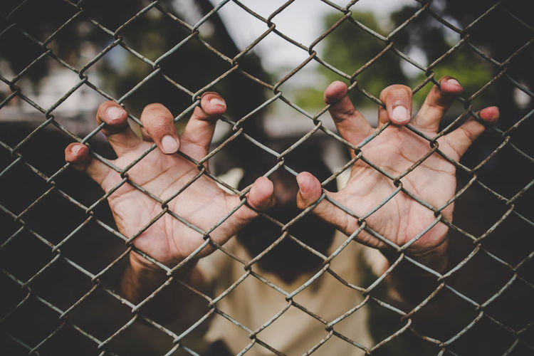 Cropped image of man touching metal fence