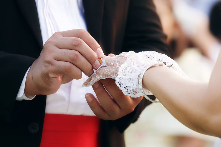 Midsection of couple during ring ceremony