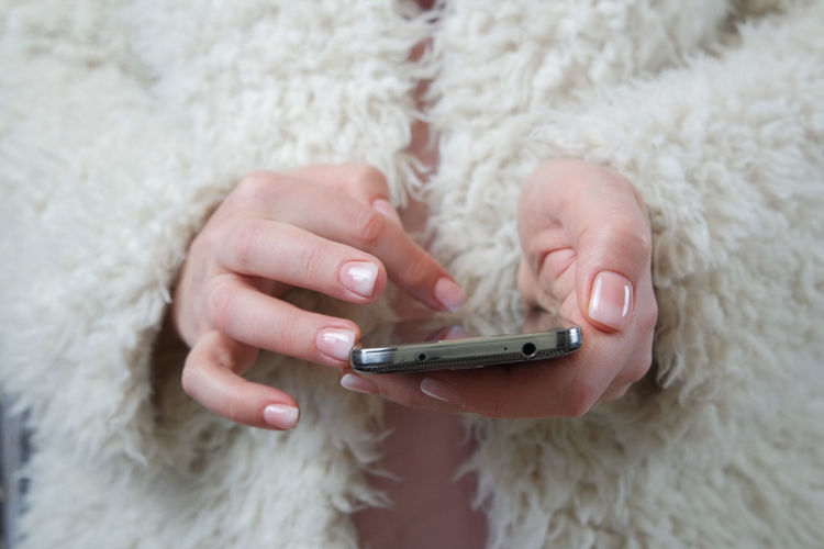 Midsection Of Woman Wearing Fur Coat While Using Smart Phone