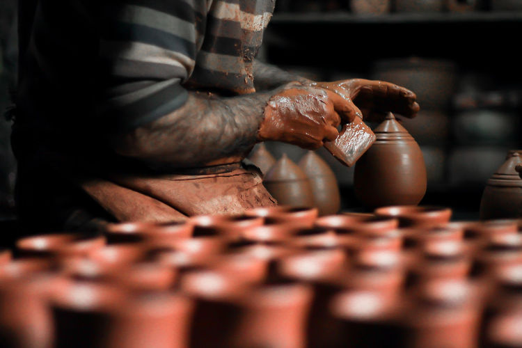 Midsection of man doing pottery in workshop