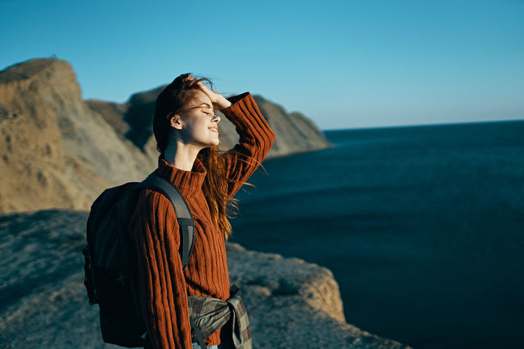 Woman looking at sea shore against sky