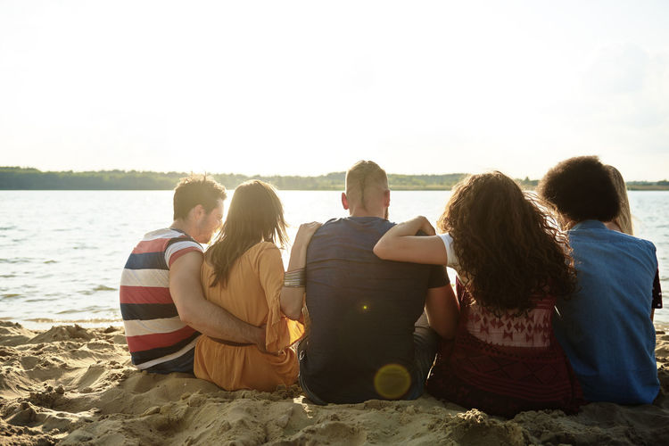Rear view of friends sitting at beach