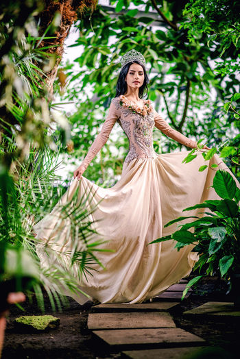 Portrait of beautiful bride wearing crown while standing on footpath amidst plants