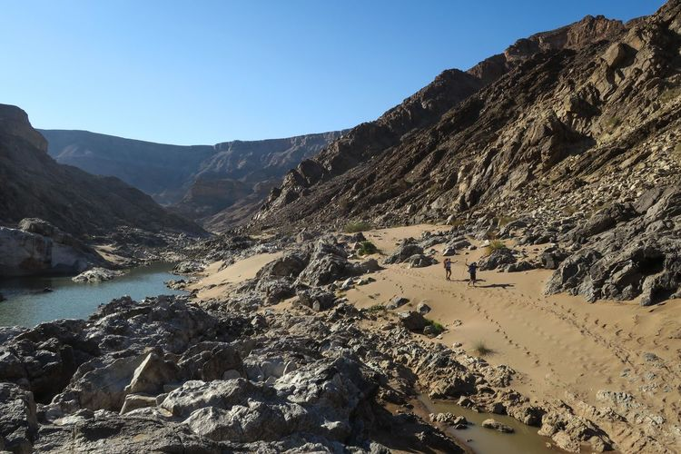 Two hikers walking alongside river in scenic desert canyon Adventure Canyon Clear Sky Explore FootPrint Hikers Hiking Landscape Landscape_Collection Let's Go. Together. Mountain Mountain Range Namibia Nature Outdoor Photography Outdoors River Rock - Object Sand Sky Tranquility Two People Walking Water Wilderness