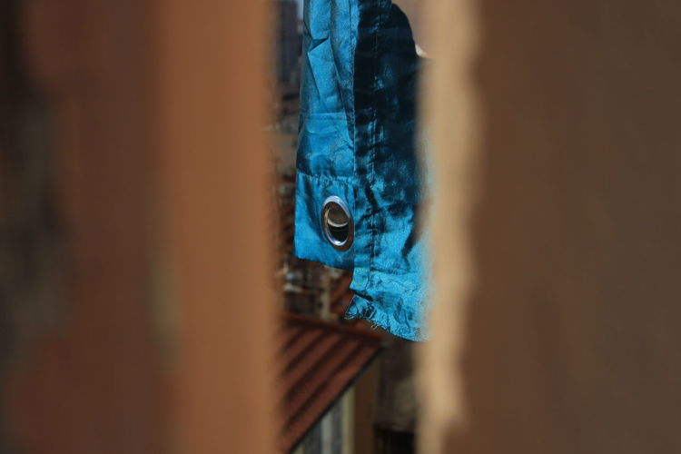 Close-up of blue fabric seen through wall